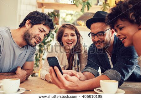 Group of young people sitting in a cafe and looking at the photos on smart phone. Young men and women meeting at cafe table and using cell phone - stock photo