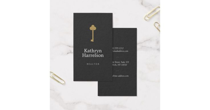 A simple logo of a vintage skeleton key in matte gold is elegantly styled with your name or business name on this realtor's, real estate, or interior designer business card template. An unique design that's sure to stand out. Set on a subtle black textured background for a vintage effect. © 1201AM CREATIVE