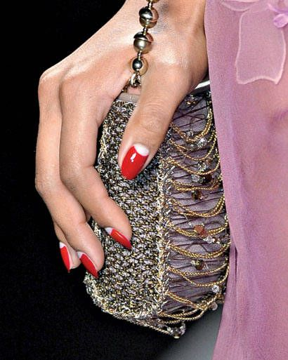 Red Polish. Half moon manicure:Use a white nail pen to mirror the natural shape of your nail bed on top of a red base, then finish with a topcoat.