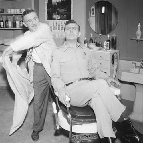 Mayberry, North Carolina's town barber Floyd Lawson (Howard McNear) readies the apron for Sheriff Andy Taylor (Andy Griffith) in this promotional photo for The Andy Griffith Show.