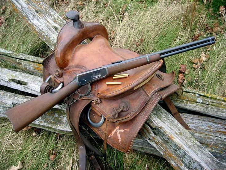 Winchester lever action rifle on saddle. Winchester is the standard for lever action rifles. lever action gun and saddle.