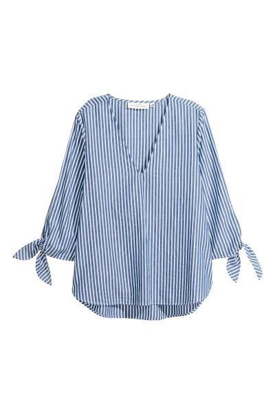Een wijde blouse van luchtig, geweven katoen met een streepdessin. De blouse heeft een diepe V-hals, driekwart mouwen met strikbandjes onderaan en een iets