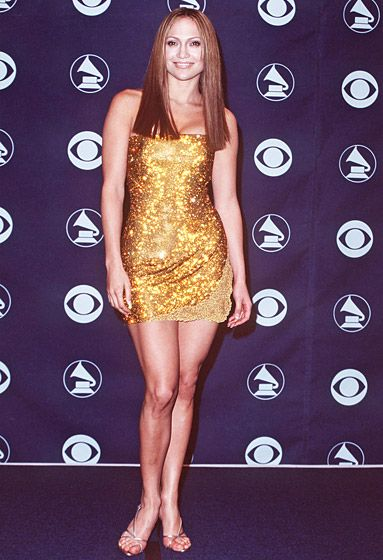 February 24, 1999 Sleek and shiny! Lopez showed off her toned, slim legs in a short gold dress at the 41st annual Grammy Awards.