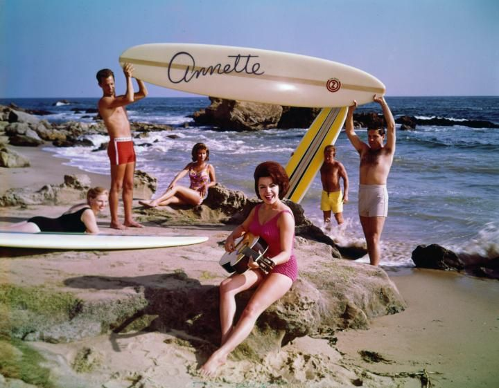 """Circa 1964: EXCLUSIVE Promotional photo of American actor and singer Annette Funicello playing an acoustic guitar on the beach as two men hold up a surfboard with her name on it, for her album, """"Muscle Beach Party."""" Other young women sit on the beach, wearing swimsuits. (Photo by Gene Lester/Getty Images)"""