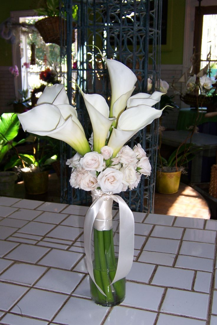 Elegant arrangement with white calla lilies and spray roses in a tall vase