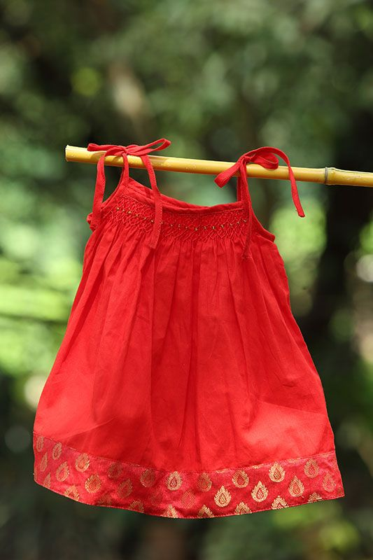 Hand smocked frock with brocade border and shoulder tie. Comes with a matching red or contrasting green brocade border. Matching panties are available.   This cotton dress is suitable for 6m+ Makes your little one as vibrant and colourful looking like the brightly coloured party girl.