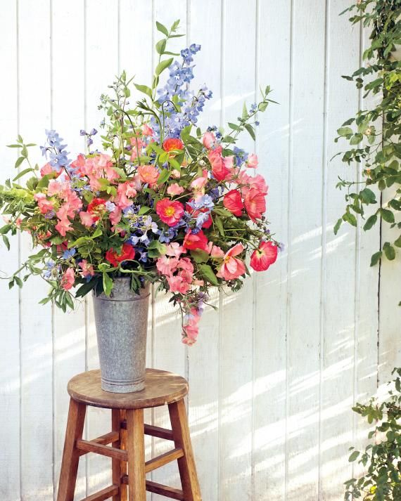 Sky-blue delphiniums, coral Icelandic poppies, and salmon-pink sweet peas are the stars of this abundant arrangement housed in a galvanized French flower bucket. Benzakein extols the merits of buying domestically grown flowers. Floret flowers.