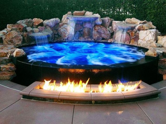 a spectacular blue jacuzzi clad with black tiles and with waterfalls
