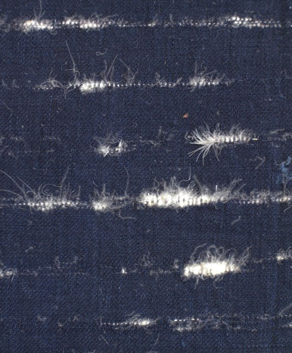 An indigo dyed cotton cloth that shows striations of woven swan feathers and down. Japan