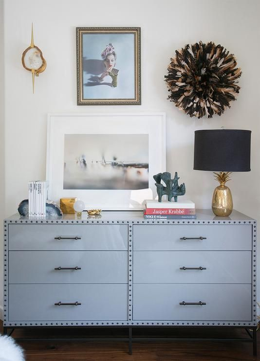 Chic bedroom dresser features an industrial gray dresser with rivets fitted with 6 drawers topped with blue quartz bookends and a gold pineapple lamp under a gold agate sconce and a brown and black juju hat.