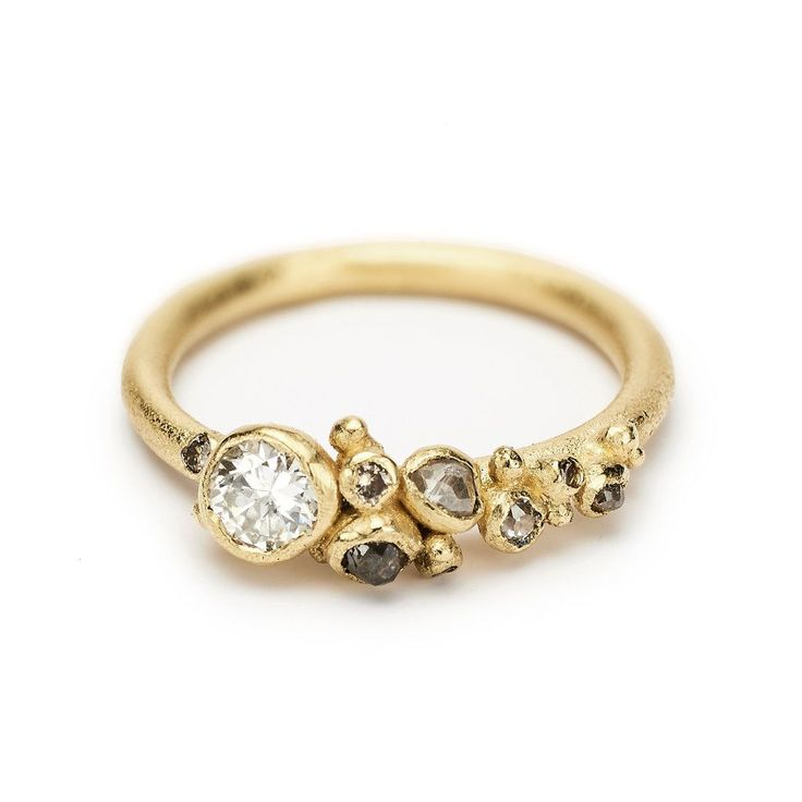 A unique asymmetrical engagement ring featuring a beautiful tapering cluster of diamonds. Handmade in London by Ruth Tomlinson.