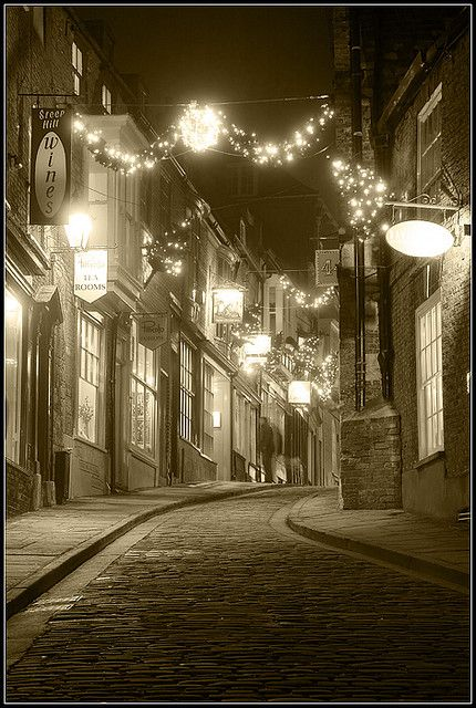Lincoln's Steep Hill lit by hanging lights at night.