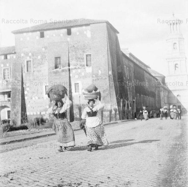 Donne con ceste, forse lavandaie, lungo la via Ostiense. Sullo sfondo il Monastero e il campanile della Basilica di San Paolo fuori le Mura fuori le Mura. Anno: 1890 ca.