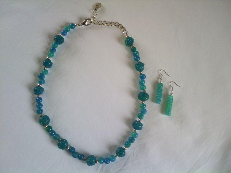 Een transparante polymeer klei ketting. De kralen zijn met blauw en groene inkt bewerkt.