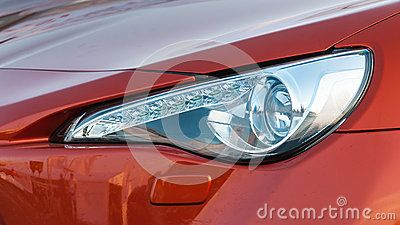 Headlight of a red modern car close up.