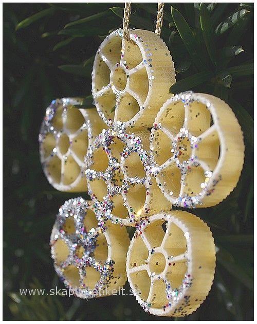 """Jag limmade ihop pastahjul till en """"snöstjärna"""". Sedan strök jag lim upplöst i lite vatten på fram och baksida och strödde glitter på. Till sist band jag ett guldsnöre i ett av pastahjulen."""