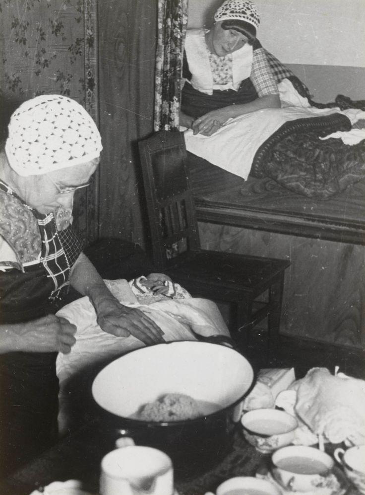 Kraamvrouw en baker omstreeks 1935. Jaren 30 moest vrouw na bevalling 14 dagen in bed blijven. Soms bleven bedgordijnen 1e week gesloten. Men was bang voor kraamvrouwenkoorts. Verzorgd door moeder of baker met oude gewoontes. Moeilijk voor moderne vroedvrouwen en artsen. Baby ingebakerd met navelbandje, verschillende hemdjes, wikkelluiers, jakje en mutsje. Bundeltje dan in dekentjes en doeken gewikkeld. Inbakeren gebeurde om het kind recht te laten groeien. #Utrecht #Spakenburg