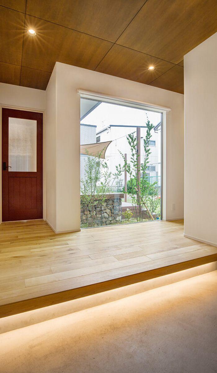玄関ホールの無垢床と 天井のベニヤ板貼り 玄関足元を照らす間接照明