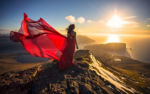 Обои Дания, Фарерские острова, девушка в красном платье стоит на горе и смотрит на закат солнца над Атлантическим океаном