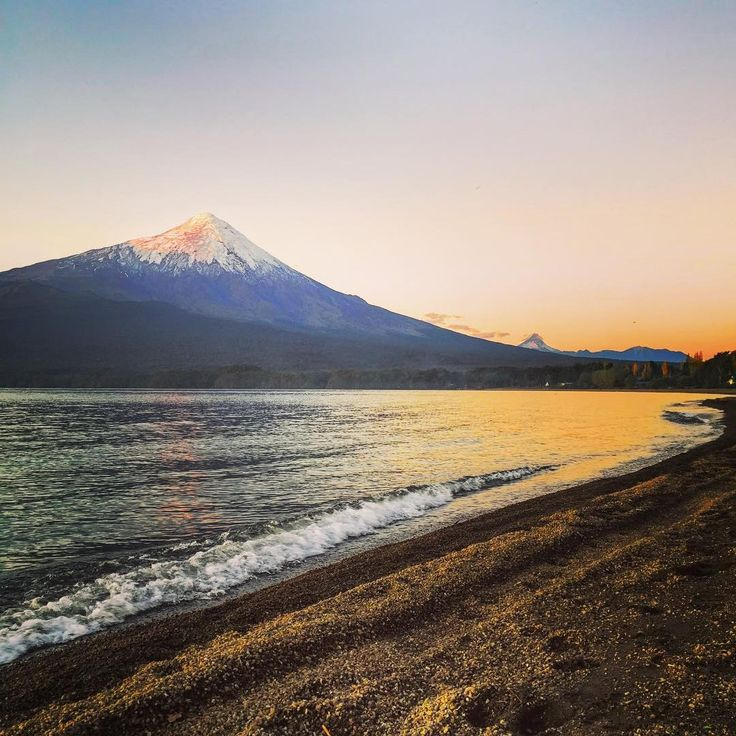 Missing Varas: Day 2  After a day of hopping on and off busses, getting stuck in blackberry bushes, and splurging on a buffet seafood dinner - I had to sit on the beach and watch the sunset over Volcan Osorno. #hiddenchile #puertovaras