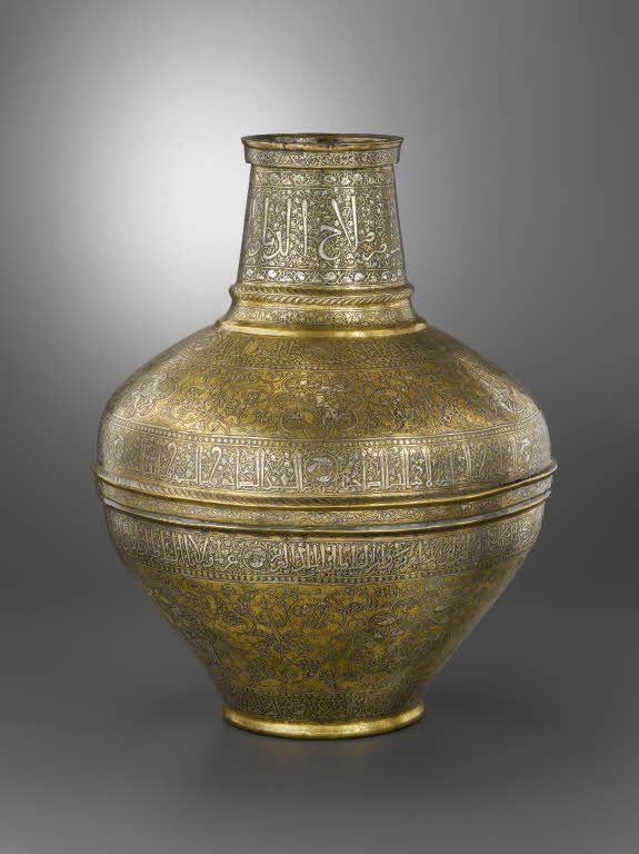 Vase dit « Barberini »  Attribué à Dawud ibn Salama al-Mawsili  1239 - 1260  Syrie, Damas ou Alep Alliage cuivreux, décor gravé et incrusté  Ce vase, unique par sa forme, présente un décor particulièrement raffiné. Les inscriptions font alterner des suites de vœux avec les titres du dernier sultan ayyubide d'Alep et de Damas, al-Nasir Salah al-din Yusuf. Les médaillons de la partie basse enferment principalement des scènes de chasse, divertissement et entraînement de l'élite militaire.