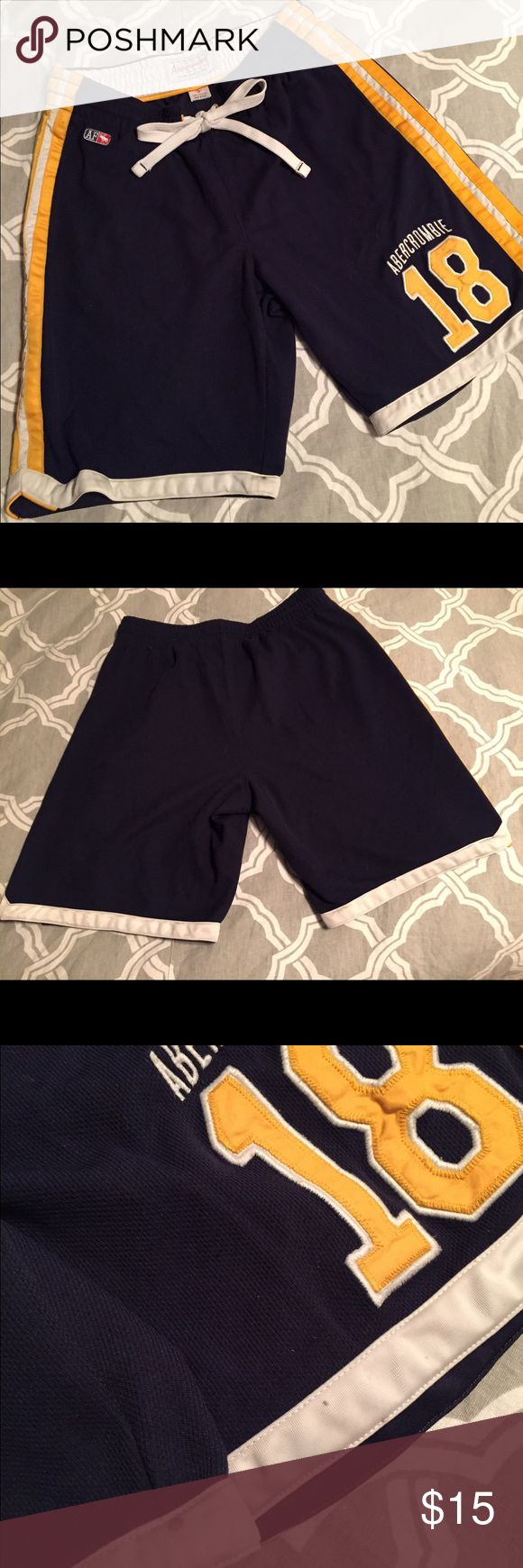 Men's Gym Shorts Navy blue, yellow and white drawstring gym shorts. 100% Polyester, thicker material. Good quality. No holes or rips but does have a few very small dark colored stains on the white and yellow areas as seen in photos #3 and #4. Similar stains noted on bottom white strip on the backside of shorts. Smoke free/pet free home. Abercrombie & Fitch Shorts Athletic