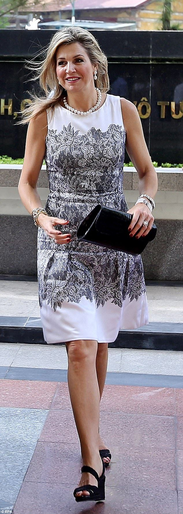 Queen Maxima wore a white dress with a floral print and black heels to meet with Vietnames...