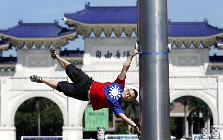 O ciclista Liao Hong-lin, de 29 anos, se apoia em um mastro em um ponto turístico de Taipei como se fosse uma bandeira enquanto veste uma camisa com as cores da bandeira de Taiwan...