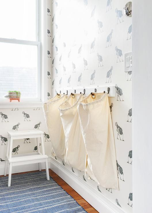 Wonderful Mounted On A Wall Covered In Beware The Moon Ostrich Wallpaper, Three  Hampers Hang On Hooks On A Wall Adjacent To A Window Positioned Above A  White Step ...