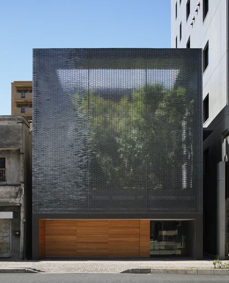 A tree-filled courtyard is glimpsed through the shimmering glass-brick facade of this house in Hiroshima, designed by Japanese architect Hiroshi Nakamura