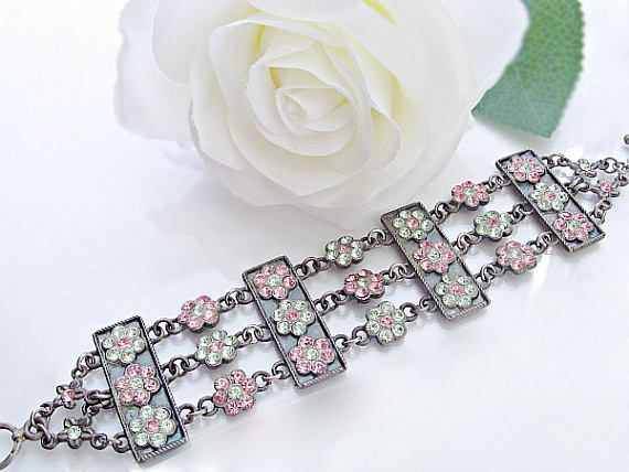 $85  Unique statement bracelet with hundreds of Swarovski shimmering crystals in pink and green. Feel instantly elegant and regal when you wear this bracelet!  www.rachelflamdesign.etsy.com