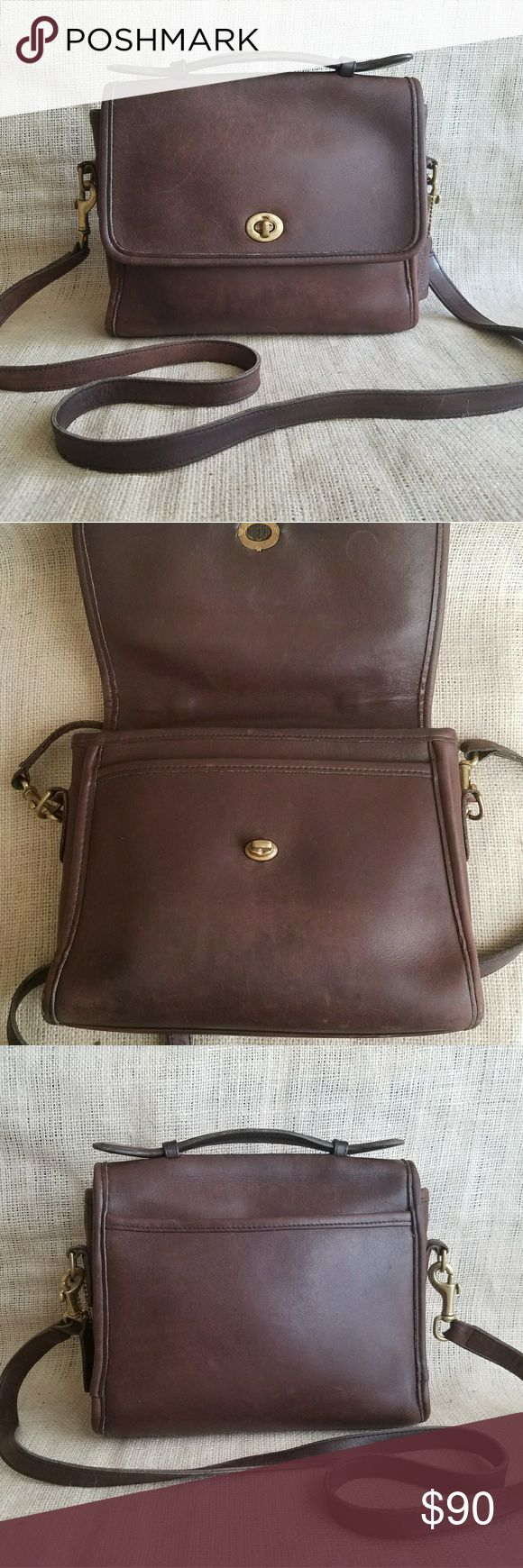 """Vintage Coach Court Crossbody Brown Leather Bag Beautiful vintage chocolate brown Coach bag in the classic Court model. The bag has wear consistent with age. I love leather that's been lived in, tells such a story! I have conditioned this bag & the color is lovely.  One main area & one small zip pocket inside. Slip pocket on back. Hang tag included. Pic shows a wear-through on bottom left piping.  Serial number is J5C 9870. Made in USA.  9.5"""" wide 8"""" tall 3.5"""" deep with a strap drop of 21""""…"""