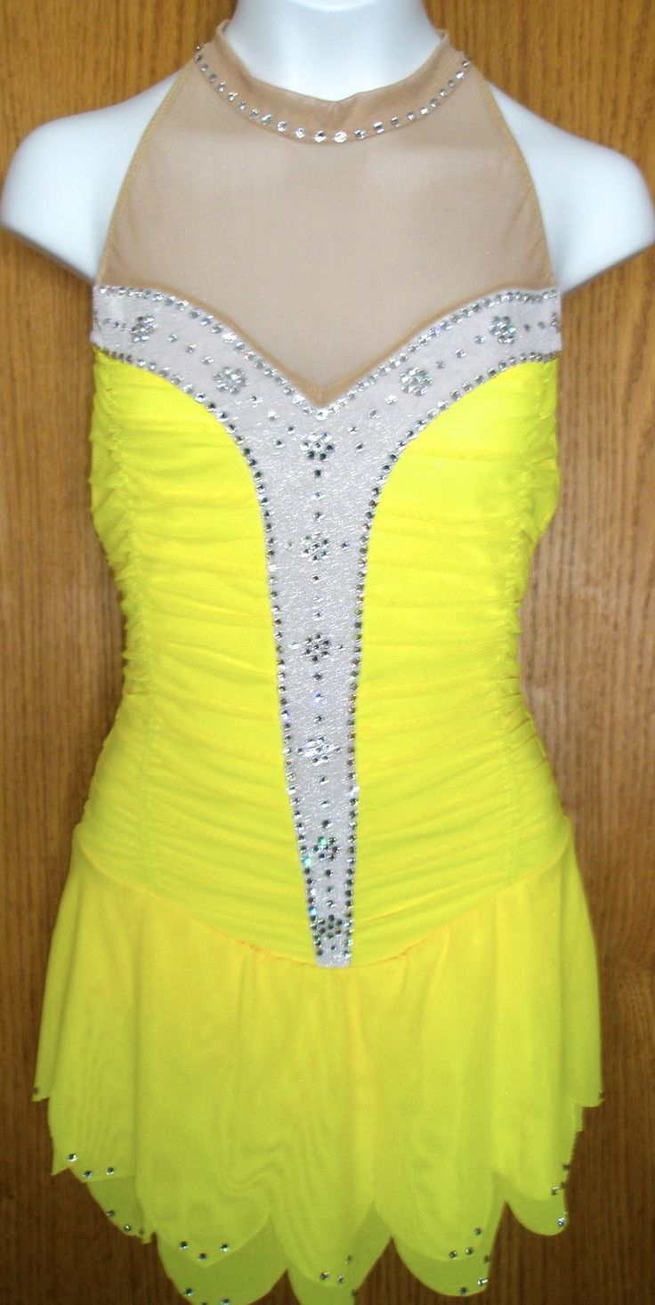 Gathered lemon yellow mesh over yellow Lycra with a white glittered velvet insert down the front. Sweetheart neckline, mock neck, petal skirt and crystal straps in back. Genuine clear swarovski crystals complete the look.
