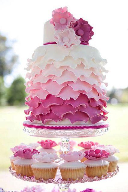 Ombre Petals Wedding Cake with cupcakes below. #weddingcake #pinkwedding