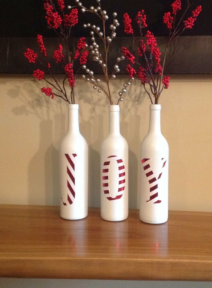 Schilder flessen wit en schilder er daarna letters op (in rood). Zo krijg je een unieke kerstdecoratie