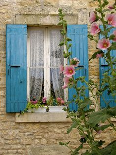 Favorites all together Hollyhocks, stone walls, pretty color shutters and lace curtains...Lovely! O Estilo Adorável Da Vida Campestre!por Depósito Santa Mariah