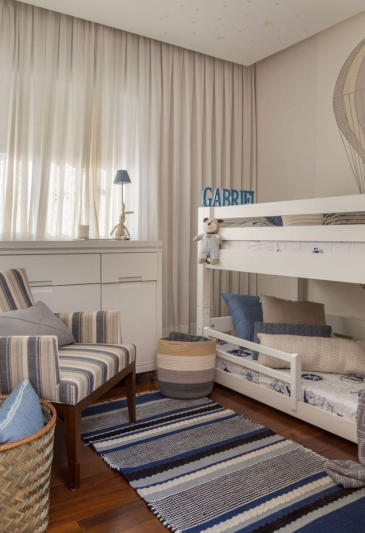Decoração com influencias brasileiras com madeira e ambientes integrados. No quarto infantil as cores usadas são azul e branco, com tapete, cesto e beliche.