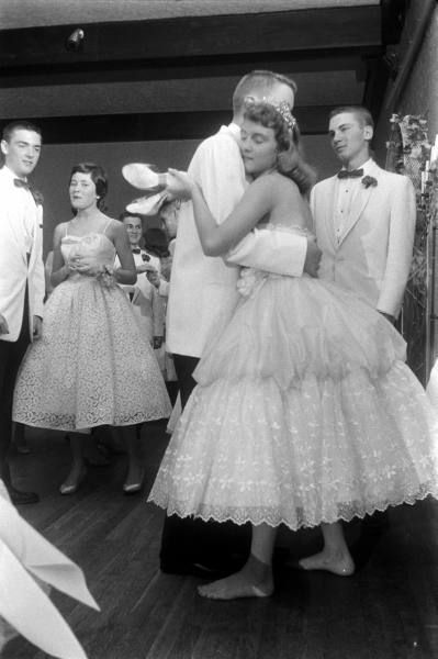 A young couple slow dancing, 1950s.