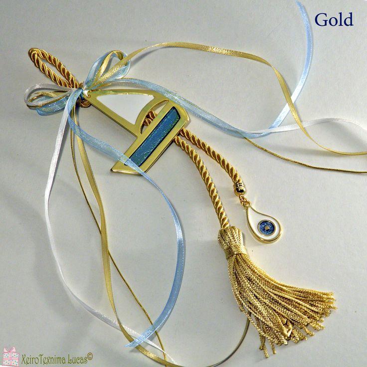 Ελληνικό, χειροποίητο γούρι σε χρυσό και σιέλ. Το γούρι αποτελείται από ένα μεγάλο μεταλλικό καράβι με λευκό και γαλάζιο σμάλτο, δεμένο με σατέν κορδέλες πάνω σε μία εντυπωσιακή χρυσή φούντα. Στην άκρη της φούντας κρέμεται ένα μεταλλικό μάτι με άσπρο και γαλάζιο σμάλτο. Περισσότερα γούρια και υλικά για γούρια θα βρείτε στο www.lucas.com.gr . Greek handmade metal good luck boat charm, with white and light blue enamel, ribbons, a gold tussel and a metal evil eye with white and light blue…