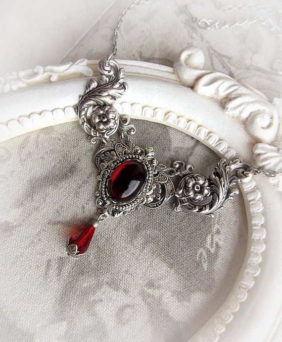 Gothic inspired necklace/choker by Midnight Vision Jewelry  It features a beautiful garnet red glass jewel in antique silver frame placed on