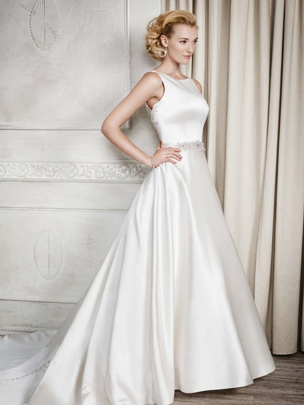 Adele- A stunning soft satin wedding gown, with a classic high neck and modern low back, buttons feature all the way down the train of the dress adding detail to the floor. Beading detail highlights the waist.