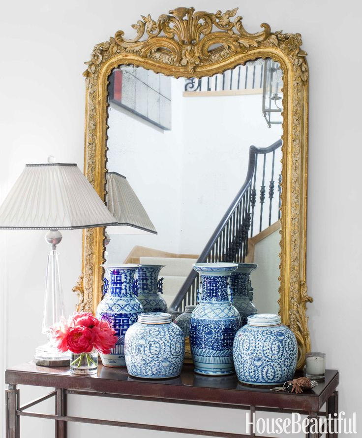 A gilded Louis XVI mirror propped on a Holland & Company table anchors the entry hall. Davenport's collection of blue-and-white porcelain from the Mews was inspired by her mother. The lamp, a family treasure, merited the trip from Texas.   - HouseBeautiful.com