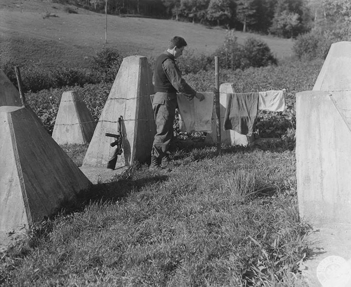 What was intended to be a formidable trap for advancing allied armies turns out to be an excellent place to dry washing. PFC Anthony Mesinko Cleveland Ohio uses the barbed wire of the 'impregnable' Siegfried Line to hang out his clothes