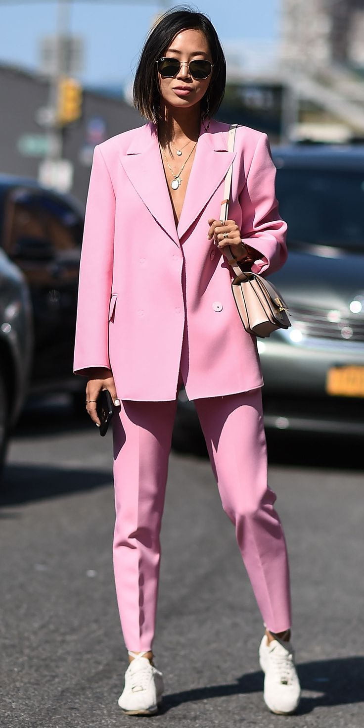 Aimee Song also wore an elevated look at New York Fashion Week. The style blogger femmed up her boxy suit by going for one rendered in Millennial pink. A pair of off duty sneakers, a neutral handbag, and rounded sunnies completed the look.
