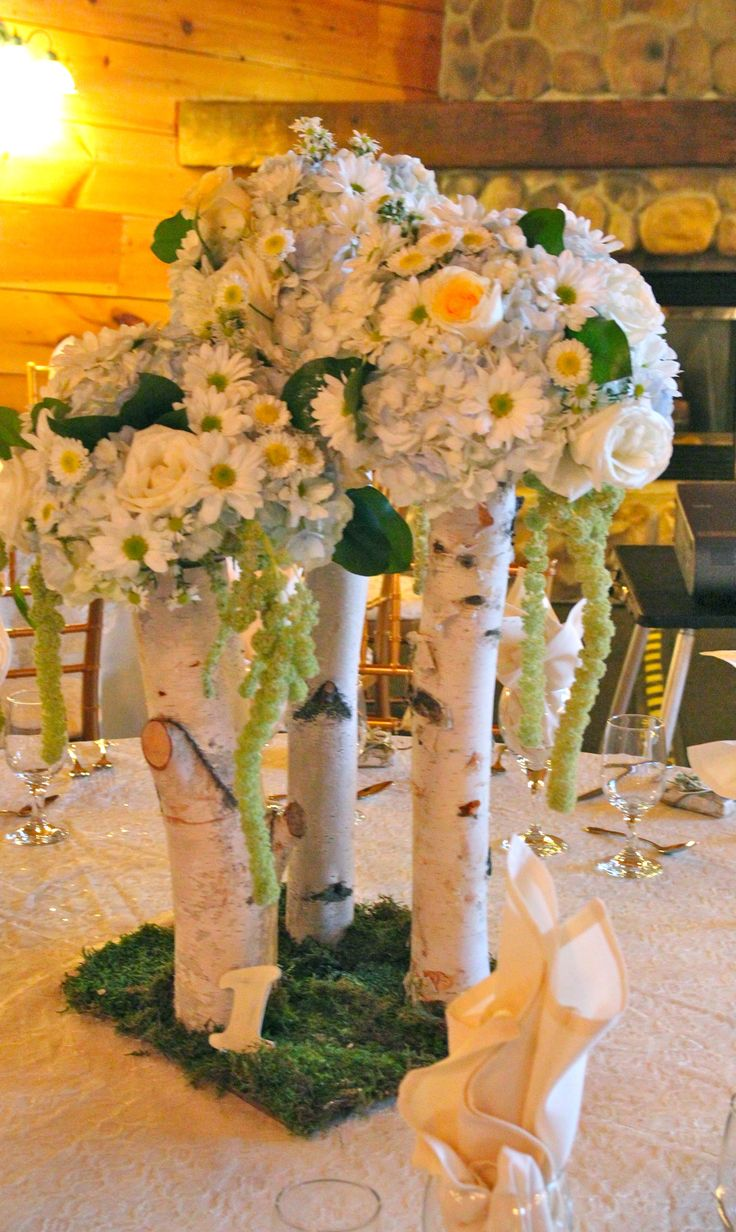 Trio centerpiece of birch logs, hydrangea, daisies, roses and hanging amaranthus