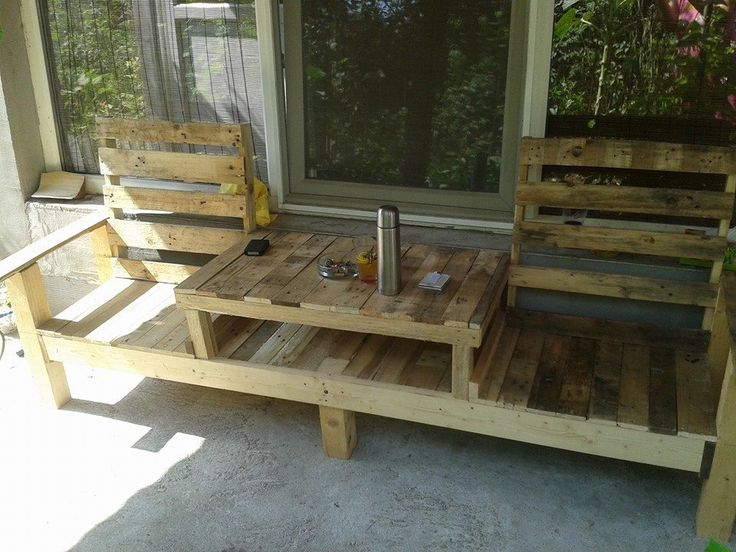 A creative bench with an integrated table in the middle, all made from reclaimed pallets.