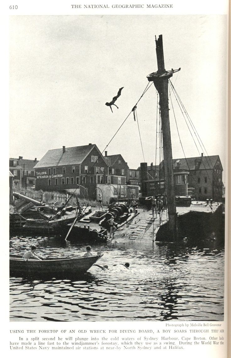 boy diving from the foretop of an old wreck into the harbour in Sydney, Nova Scotia, Canada