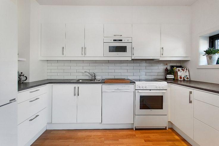 Lyst og innbydende kjøkken med mye skap og benkeplass. Kjøkkenet har hvite fronter, fliser mellom over og underskap og godt med lys. Solid hvit | Drømmekjøkkenet