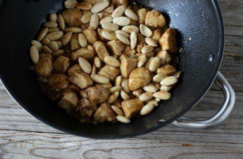 Il pollo alle mandorle saltato nel wokPollo (petto) 400 g Mandorle pelate 80 g Cipolle 1/2 Farina di riso 2 cucchiai Soia (salsa) 50 ml Acqua calda 2 cucchiai Olio di semi 3 cucchiai Zenzero fresco Quanto basta Sale Quanto basta