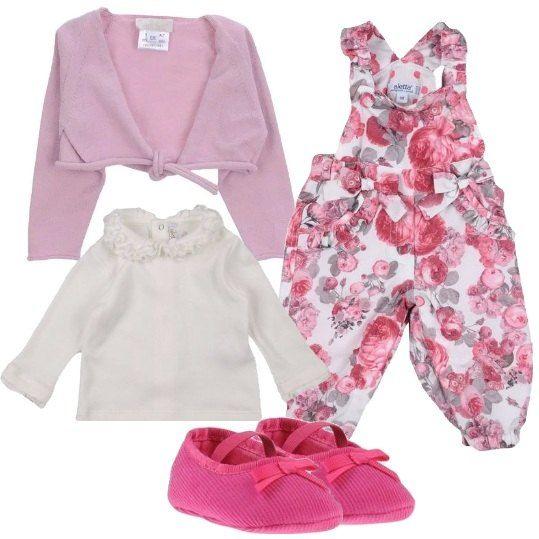 Una bellissima salopette a fiori rosa è abbinata a una magliettina con collo a ruches in cotone, uno scaldacuore di maglia leggera e scarpine di tessuto con elastici.